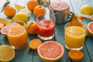 Glasses of orange juice, grapefruit juice and multivitamine juice, juice squeezer and fruits on wood
