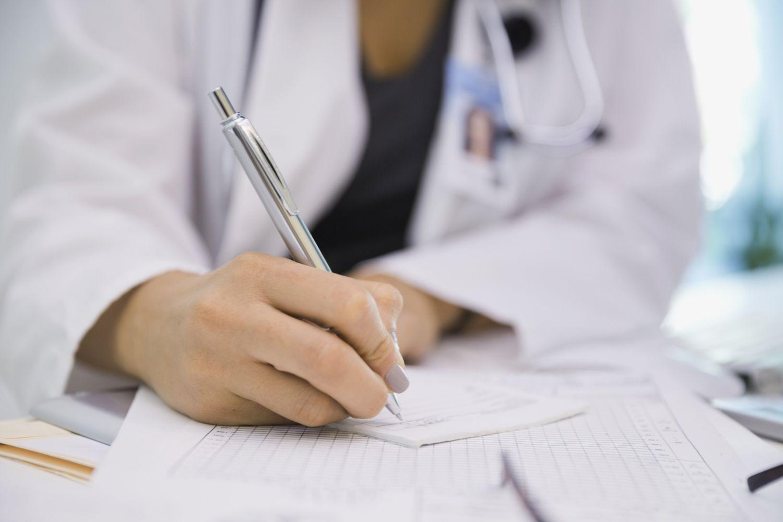 A doctor filling out a prescription