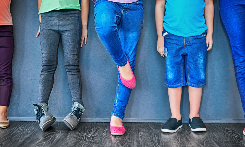 The legs of five young teens standing against a wall