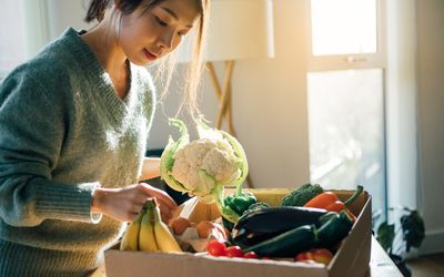 woman picks vegetables from a box