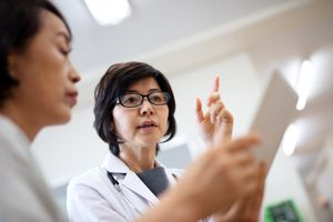 female doctor looking at paper with patient