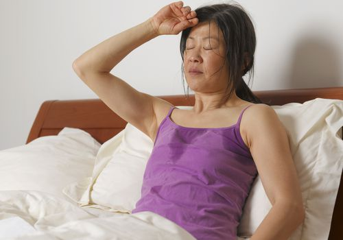Woman sweating in bed