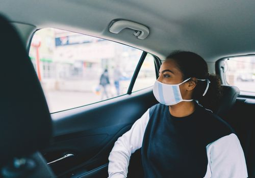 woman in the back of a car with mask on