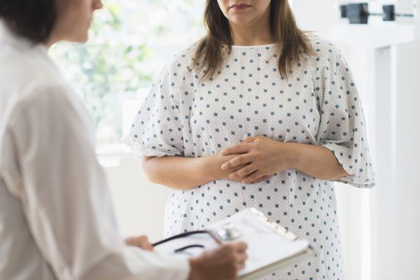 Woman meeting with doctor holding stomach in discomfort