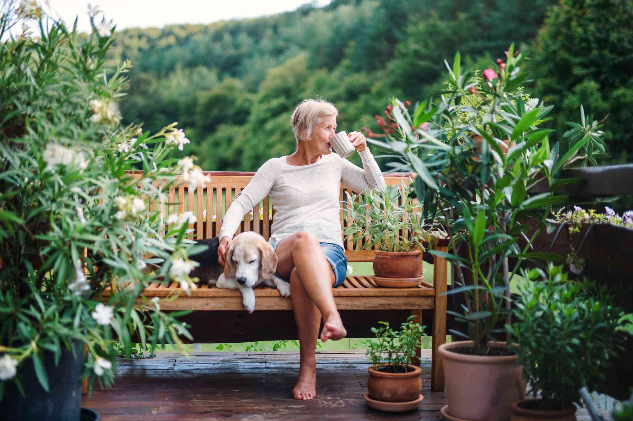 woman relaxes in nature with dog