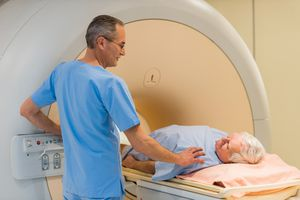 Radiologist consoling a senior patient at MRI scan.