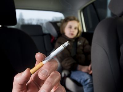 Young child being exposed to secondhand smoke