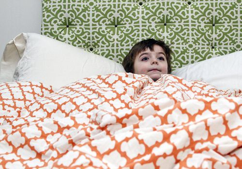 young boy lying in bed with eyes open