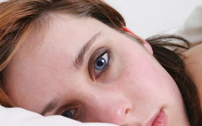 Close-up of a young woman lying in bed, staring blankly at the camera.