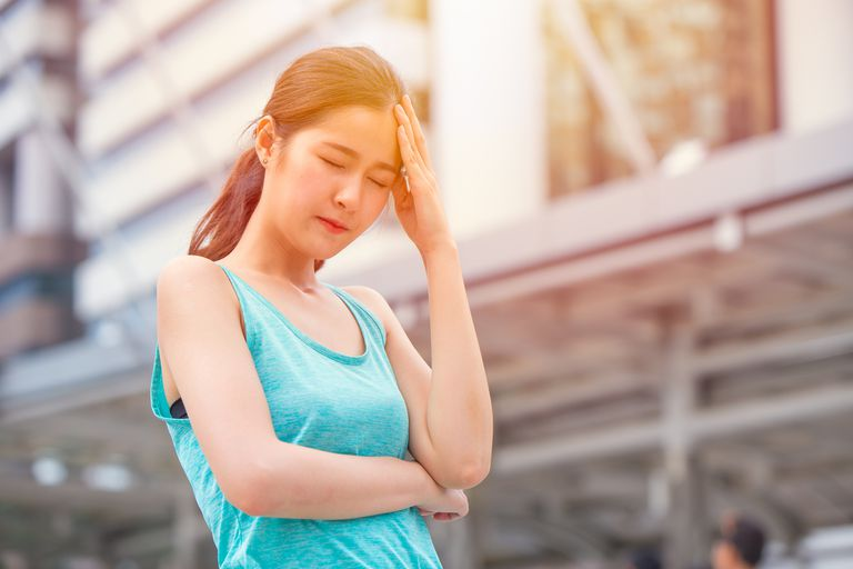 Girl holding her head on a sunny day possibly suffering from heatstroke