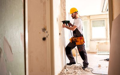 Experienced worker using hammer drill
