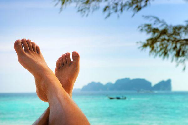 A man's feet up at the beach