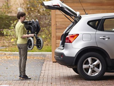 Photo of a woman loading a wheelchair into a car.
