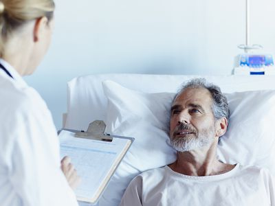 doctor writing notes while talking to male patient : Stock Photo CompEmbedShareAdd to Board Caption:Female doctor writing notes while talking to male patient in hospital ward Doctor writing notes while talking to a patient
