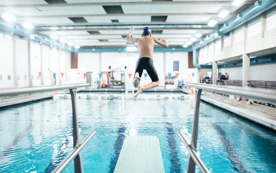 Boy jumping off a diving board into an indoor pool