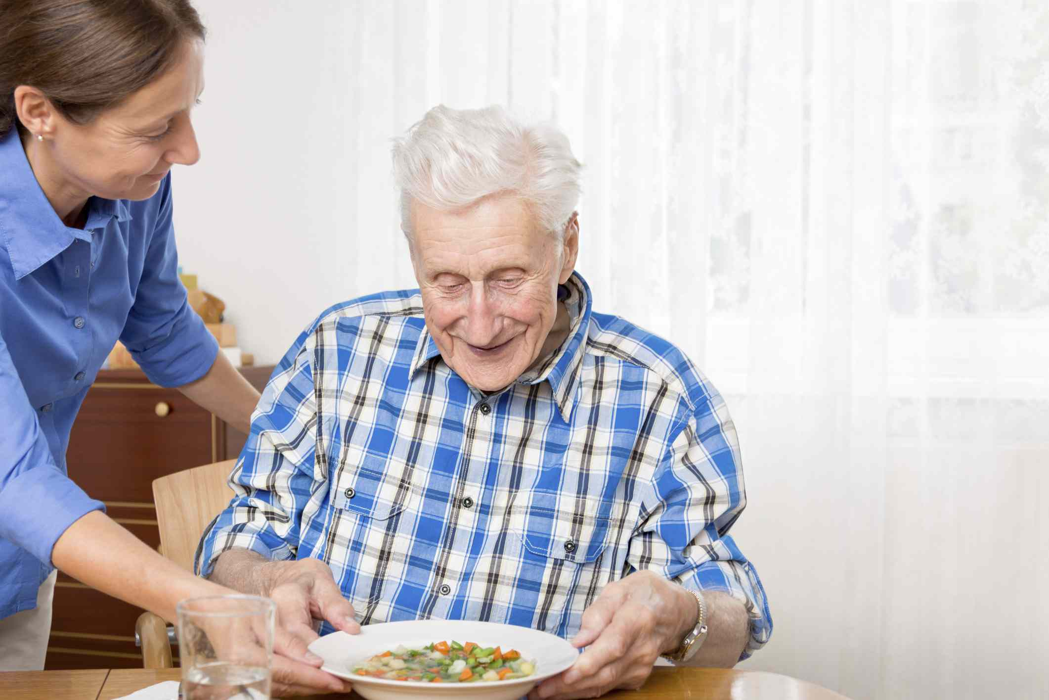 A woman helping an older man with Alzheimer's disease eat his dinner