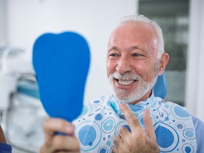 man looking at teeth and smiling