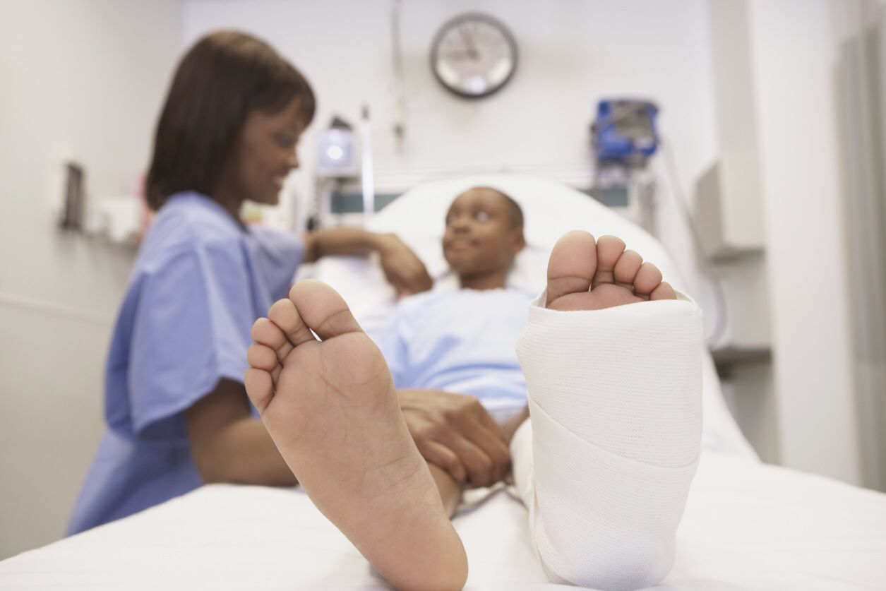 Photo of a nurse comforting patient with a broken foot