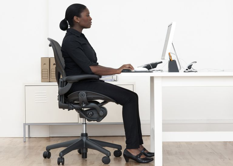 Woman sitting at a desk with laptop.