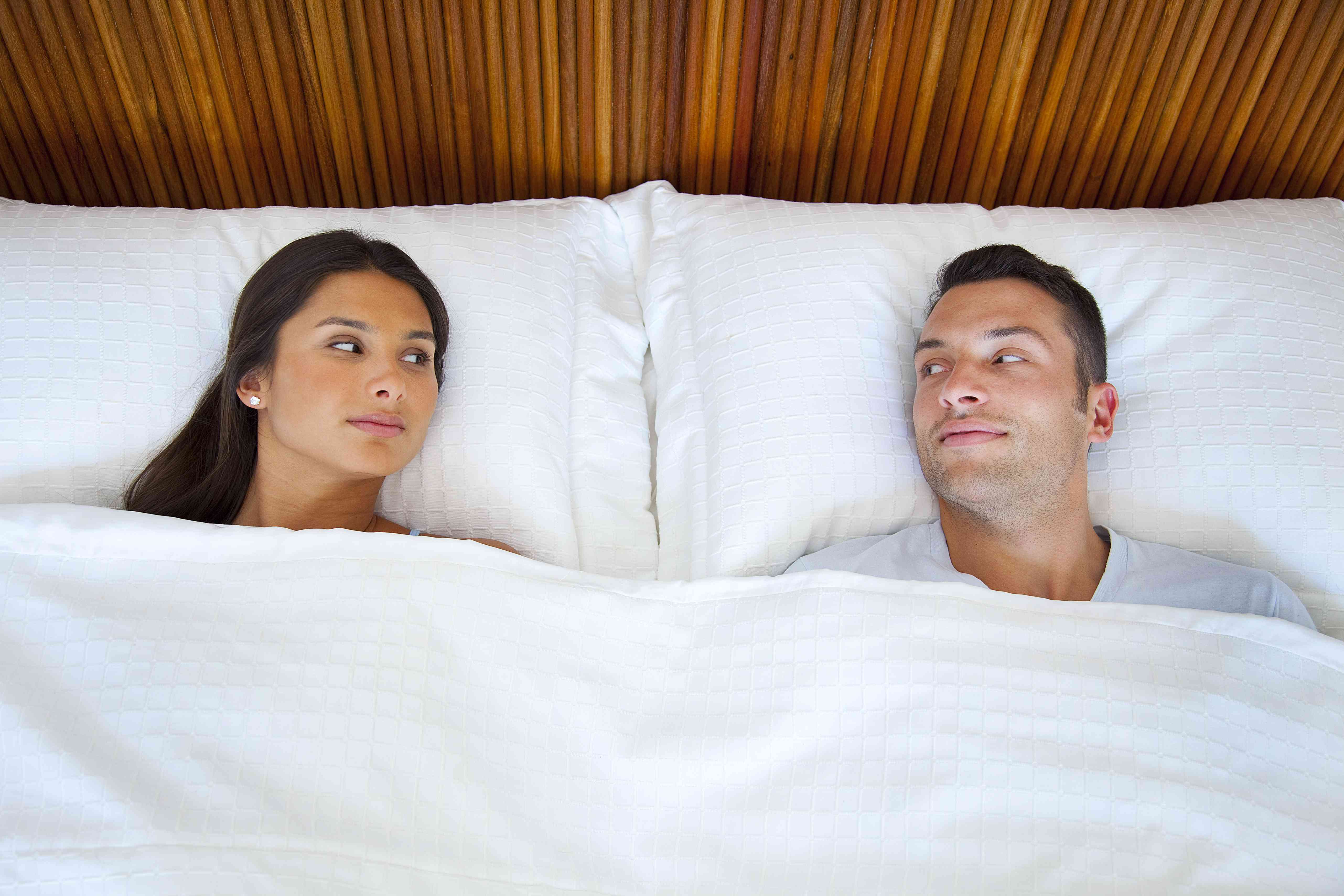 A couple laying in bed and looking at each other