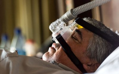man sleeping with CPAP machine on his face
