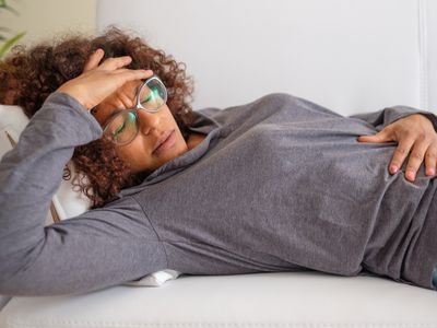 Woman lays down, her eyes closed and a hand on her forehead. Her other hand is cradling her stomach.