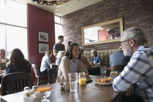 Grandfather and teenage granddaughter talking, eating brunch at diner table