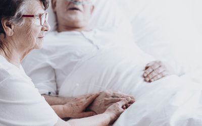 Woman holding man's hand in bed