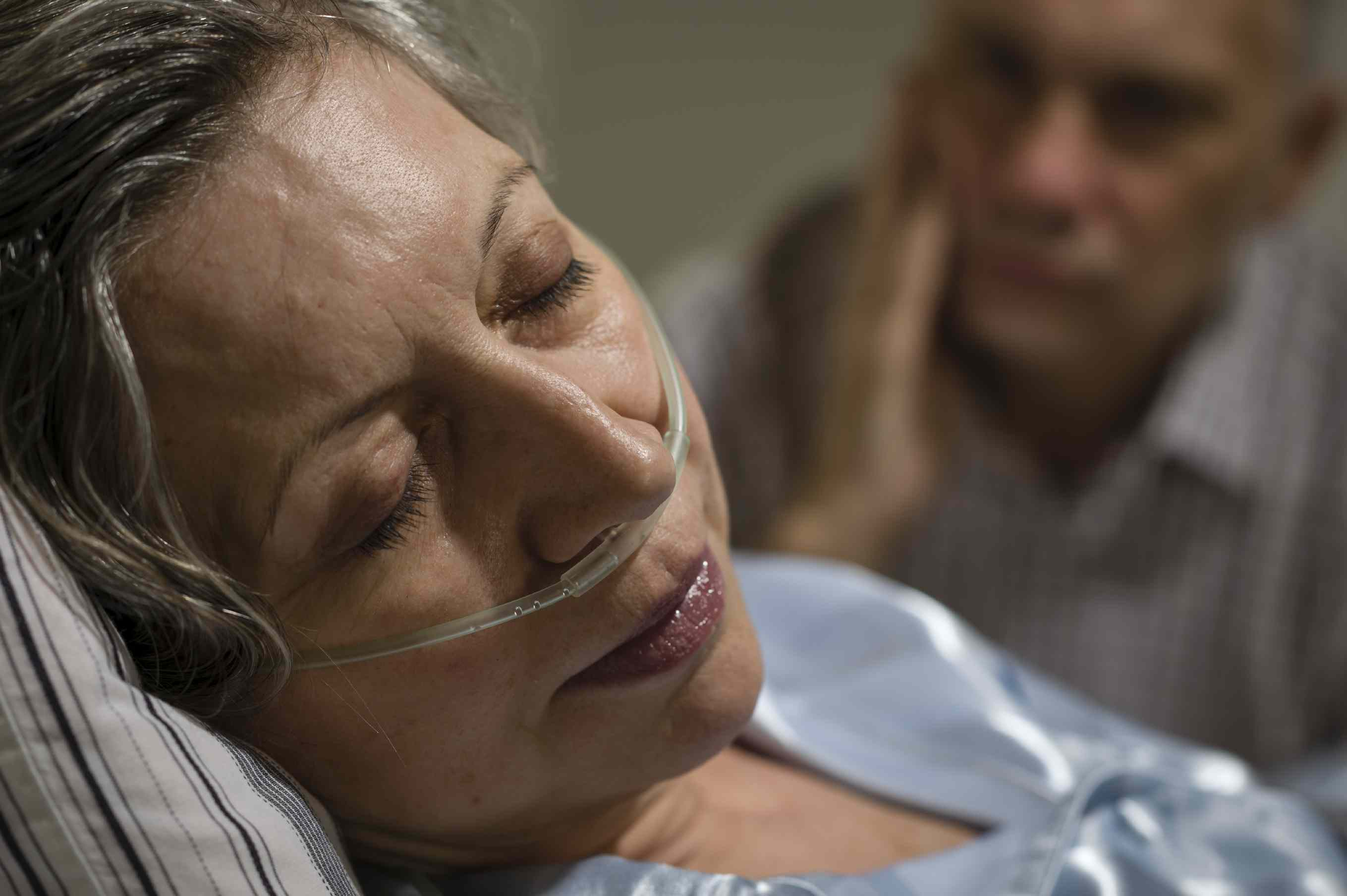 Woman on oxygen in a hospital bed with man in the background looking at her