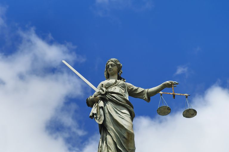 Scales of Justice Statue against blue sky with clouds
