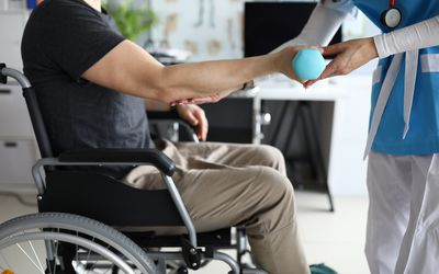 Female nurse helps lift dumbbell to disabled patient rehabilitation therapy