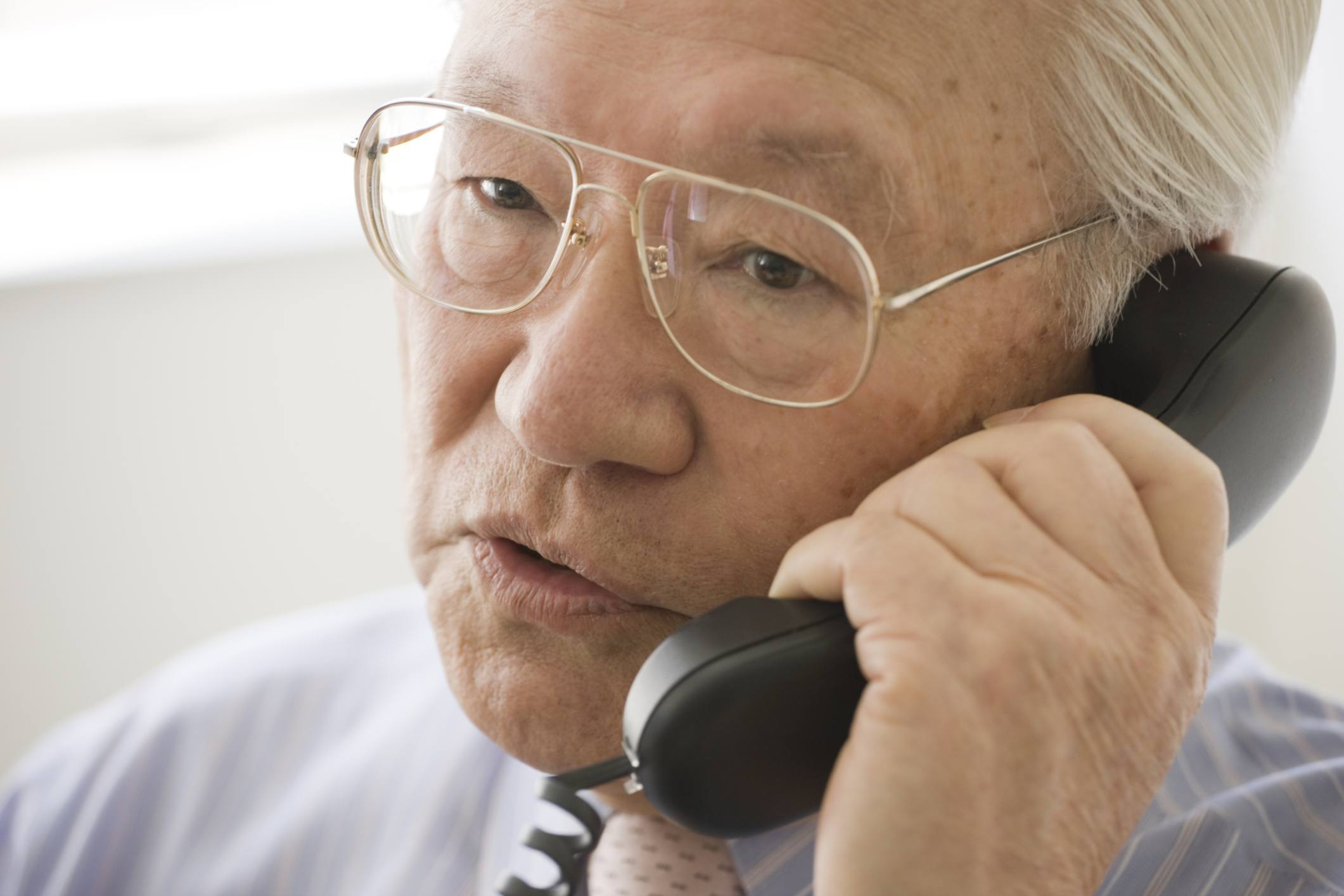 Elderly Asian man on telephone