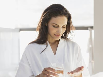 Woman taking pill in the morning