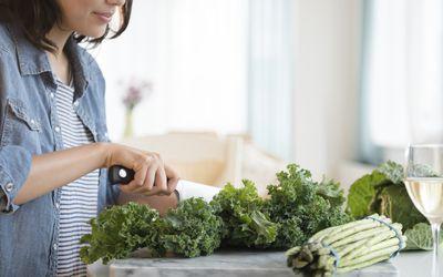 Hispanic woman chopping salad greens