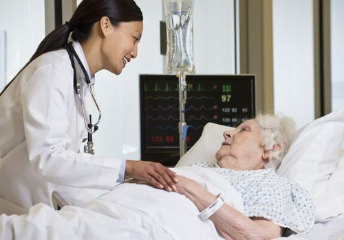 Doctor caring for elderly hospital patient