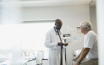 Doctor reviewing medical chart with senior man.