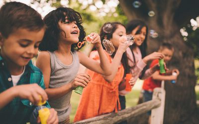 Little boy having fun with friends in park blowing bubbles