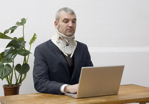 Computer worker wearing a neck brace