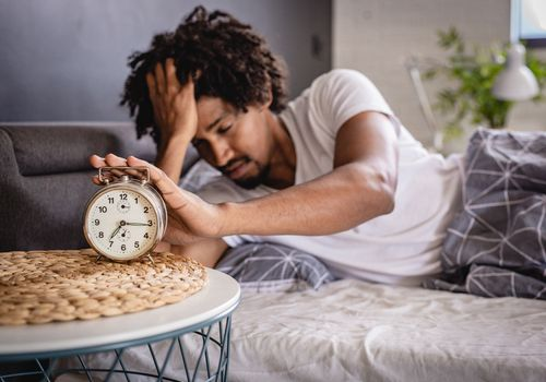 Photo of a tired man turning off his alarm clock in the morning