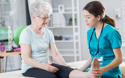 Young doctor examines senior patient's leg.