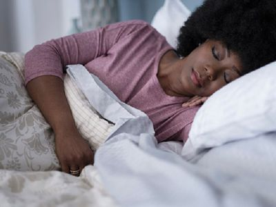 A woman sleeping in her bedroom may fall asleep and experience hypnagogic hallucinations due to narcolepsy