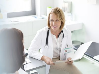 Doctor with medical chart talking with patient in examination room