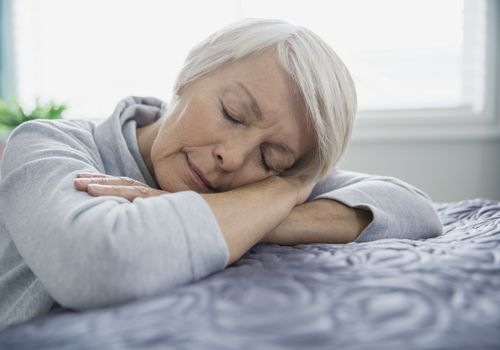 Tired SENIOR woman laying on bed with eyes closed