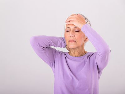A senior woman wearing a purple shirt holds her head with both hands and closes her eyes in discomfort.