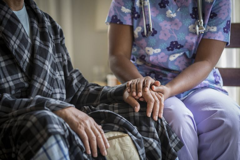 African American nurse holding patient's hand