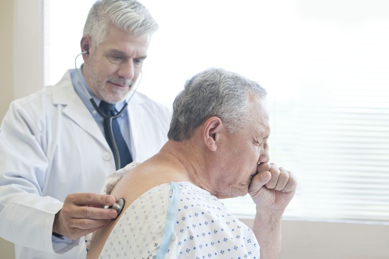 man coughing while doctor checks, a symptom of small cell lung cancer