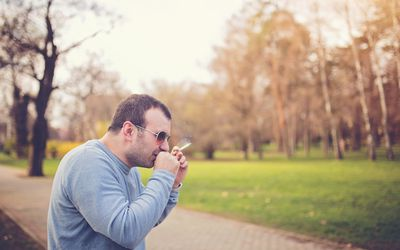 Man smoking a cigarette in a park and coughing, on a spring day