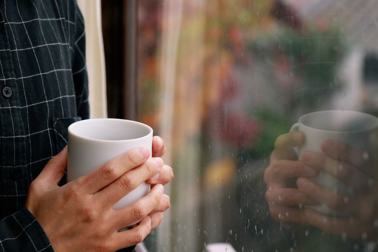 Man holding coffee mug by window with raindrops