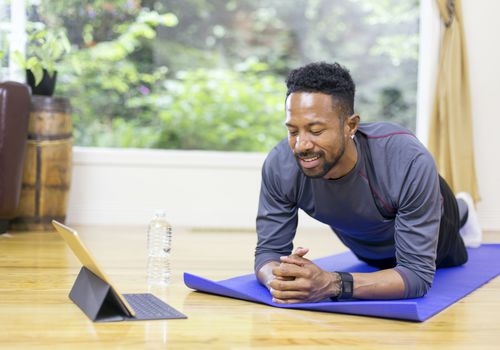 Man doing a plank exercise while watching a tablet computer