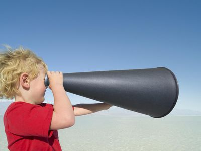 a child holding a cone up to his eye